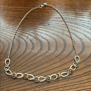 Silver necklace with gold and rose gold accents.